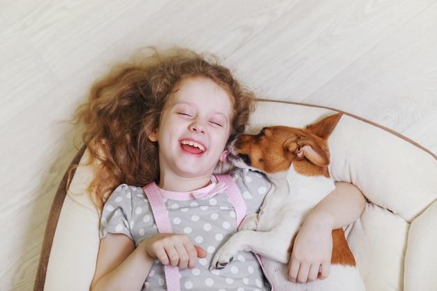 Lachendes mädchen, das einen hund, liegend auf hölzernem hintergrund umarmt und küsst. Premium Fotos