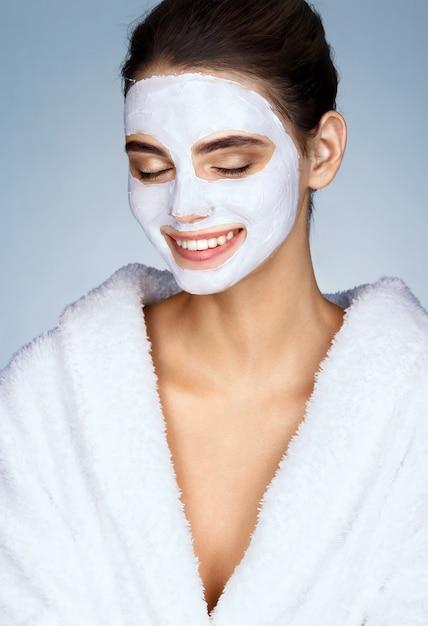 Lachendes mädchen mit befeuchtender gesichtsmaske Premium Fotos