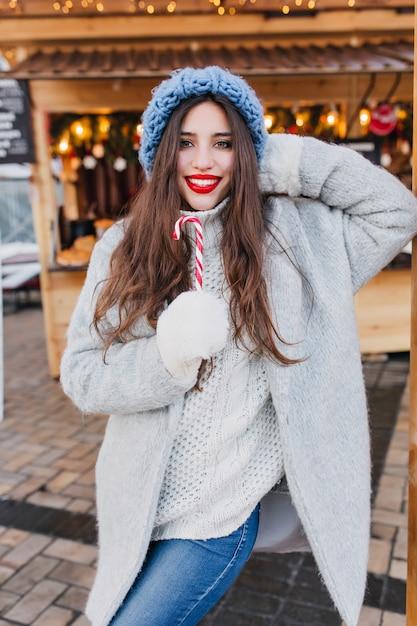 Lachendes weibliches modell mit dunkelbraunem haar, das an kaltem tag weihnachtssüßigkeiten isst. porträt des fröhlichen brünetten europäischen mädchens im grauen mantel und in den weißen handschuhen, die mit lutscher im wintermorgen aufwerfen. Kostenlose Fotos