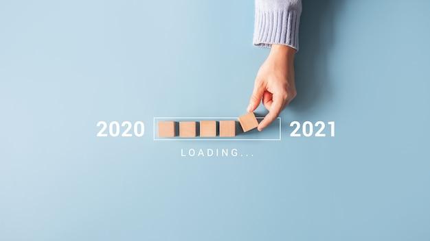 Laden des neuen jahres 2020 bis 2021 mit der hand, die den holzwürfel in den fortschrittsbalken legt. Premium Fotos