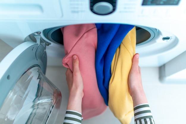 Laden von farbiger kleidung und wäsche in die waschmaschine. wäsche zu hause waschen. draufsicht Premium Fotos