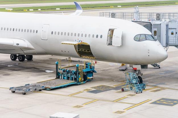 Ladeplattform der luftfracht zum flugzeug. lebensmittel für den flug-check-in und ausrüstung, die vor dem einsteigen in das flugzeug bereitstehen. Premium Fotos