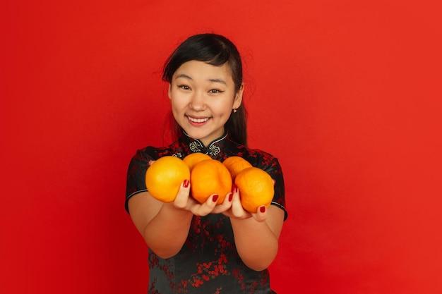 Lächeln, mandarinen geben. frohes chinesisches neujahr. asiatisches junges mädchenporträt auf rotem hintergrund. weibliches modell in traditioneller kleidung sieht glücklich aus. copyspace. Kostenlose Fotos