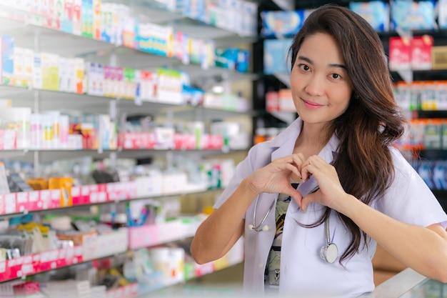 Lächeln und glücklich vom asiatischen weiblichen apotheker, der herzgeste mit zwei händen in der apotheke zeigt Premium Fotos