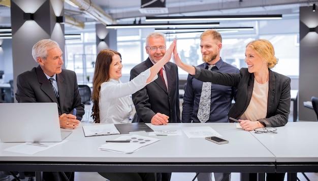 Lächeln zwei junge frauen, die hohen fünf im büro sich geben Kostenlose Fotos