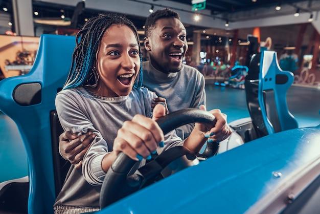 Lächelnafroamerikanermädchen, das blaues auto in der säulengang reitet. Premium Fotos