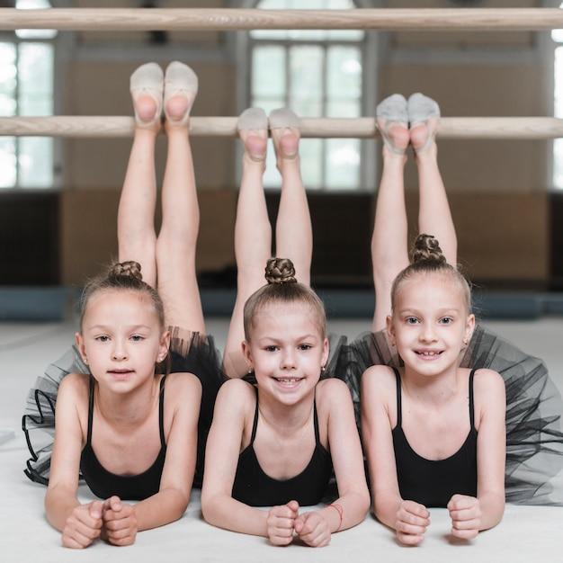 Lächelnd drei ballerinamädchen, die ihre beine auf barre ausdehnen Kostenlose Fotos
