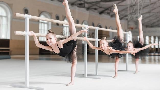 Lächelnd drei mädchen mit ihrem bein in ballett-klasse üben Kostenlose Fotos