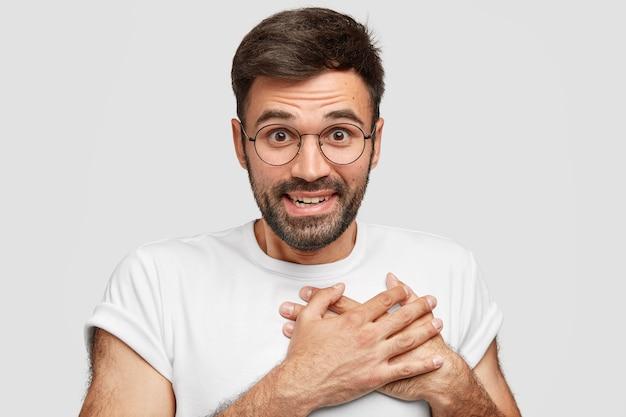 Lächelnd freundlich aussehender mann mit stoppeln, hält hände auf der brust, drückt dankbarkeit aus, hat glücklichen ausdruck, trägt lässiges t-shirt, hat dunklen bart, isoliert auf weißer wand. anerkennungskonzept Kostenlose Fotos