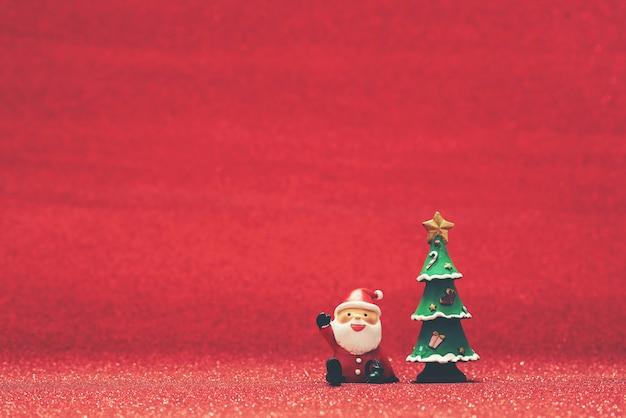 Lächelnd santa claus neben einem weihnachtsbaum und roten hintergrund Kostenlose Fotos