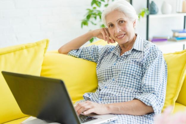 Lächelnde ältere frau, die auf sofa mit laptop sitzt Kostenlose Fotos