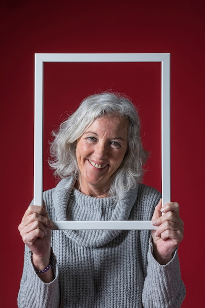 Lächelnde ältere frau, die weißen grenzrahmen vor ihrem gesicht gegen roten hintergrund hält Kostenlose Fotos