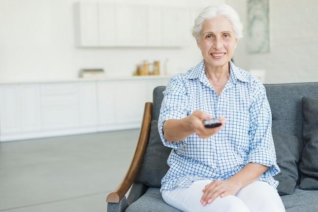 Lächelnde ältere frau, die zu hause auf sofa unter verwendung der fernbedienung sitzt Kostenlose Fotos