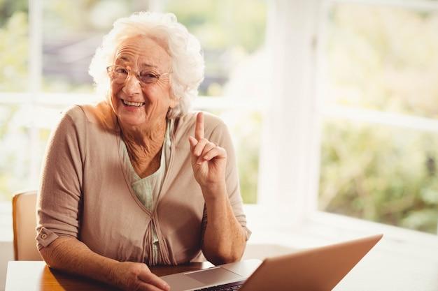 Lächelnde ältere frau, die zu hause finger unter verwendung des laptops anhebt Premium Fotos
