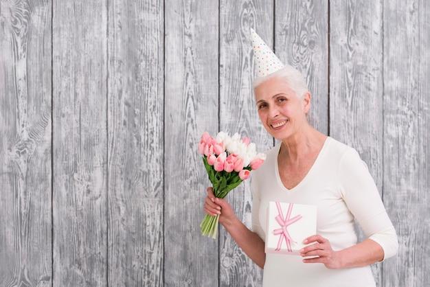 Lächelnde ältere geburtstagsfrau, die tulpenblumenblumenstrauß und -geschenkbox vor hölzernem hintergrund hält Kostenlose Fotos