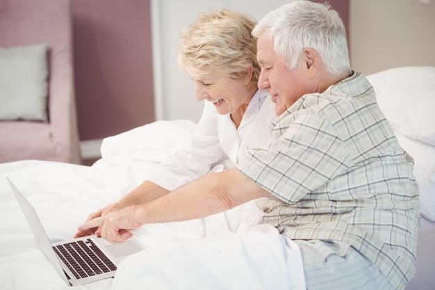 Lächelnde ältere lachende paare bei der anwendung des laptops Premium Fotos