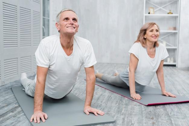 Lächelnde ältere paare, die übung zu hause ausdehnend durchführen Kostenlose Fotos