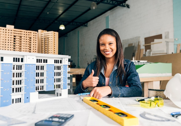 Lächelnde african-americanfrau, die daumen herauf nahe modell des gebäudes zeigt Kostenlose Fotos