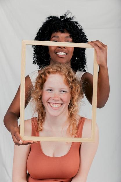 Lächelnde afrikanische junge frau, die holzrahmen vor kaukasischer frau hält Kostenlose Fotos