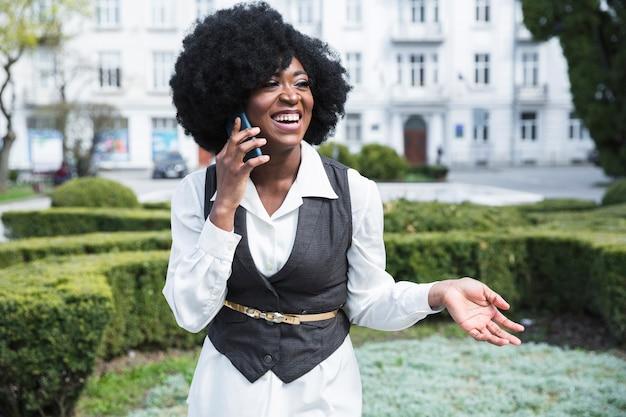 Lächelnde afrikanische junge geschäftsfrau, die am handy spricht Kostenlose Fotos