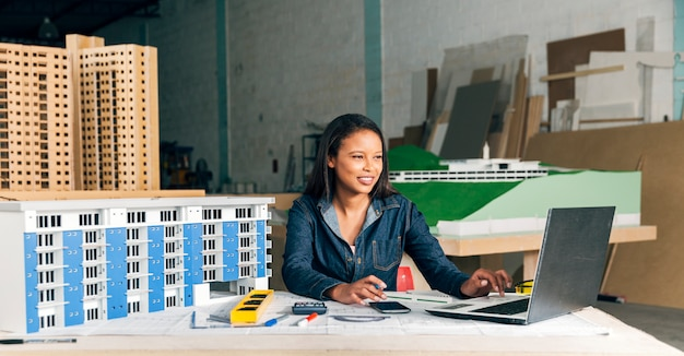 Lächelnde afro-amerikanische dame mit laptop und modell des gebäudes Kostenlose Fotos