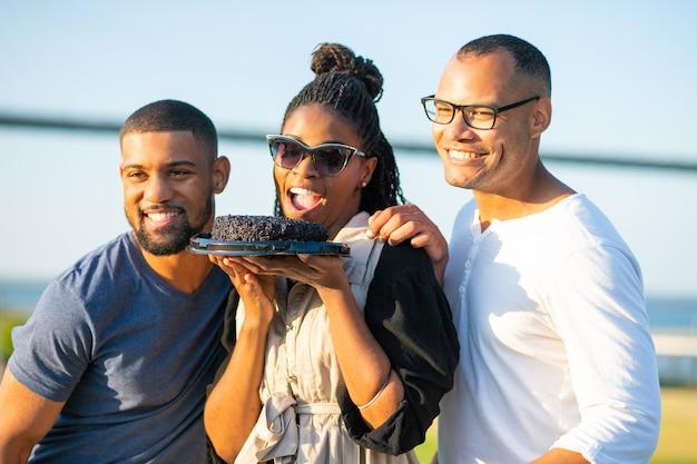 Lächelnde afroamerikanerfrau, die schokoladenkuchen hält. glückliche junge leute, die zusammen aufwerfen. geburtstagsfeier Kostenlose Fotos