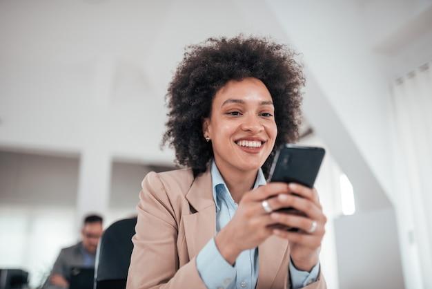 Lächelnde afroamerikanergeschäftsfrau, die intelligentes telefon in co-arbeitsbüro, niedrige winkelsicht verwendet. Premium Fotos