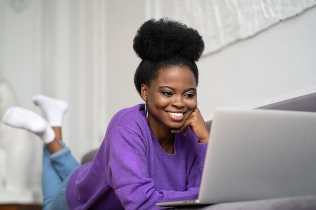 Lächelnde afroamerikanische frau mit afro-frisur tragen lila pullover, der auf sofa liegt, sich ausruht und webcam betrachtet Premium Fotos