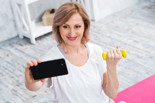 Lächelnde alte frau mit den dummköpfen, die selfie unter verwendung des handys nehmen Kostenlose Fotos