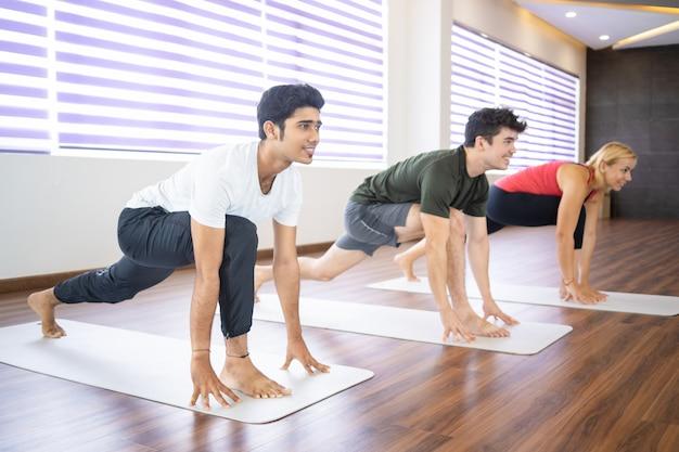 Lächelnde anfänger, die yoga an der klasse üben Kostenlose Fotos