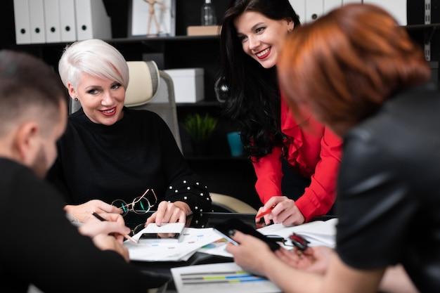 Lächelnde angestellte, die an arbeitsplatz sprechen Premium Fotos