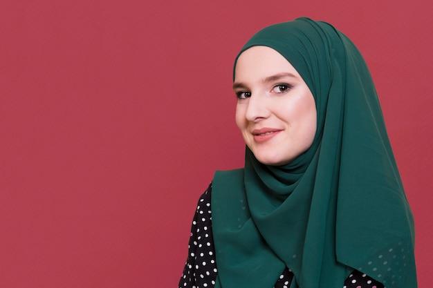Lächelnde arabische frau, die kamera betrachtet Kostenlose Fotos