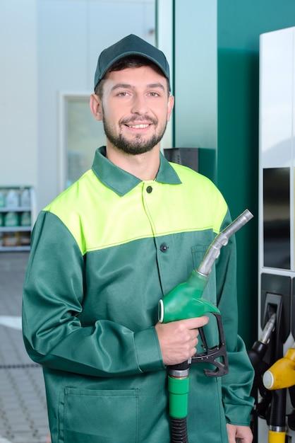 Lächelnde arbeitskraft an der tankstelle, beim füllen eines autos Premium Fotos