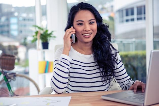 Lächelnde asiatin beim telefonanruf, der die kamera im büro betrachtet Premium Fotos