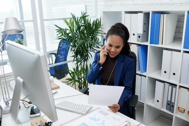 Lächelnde asiatin, die am schreibtisch im büro sitzt, dokument betrachtet und am handy spricht Kostenlose Fotos