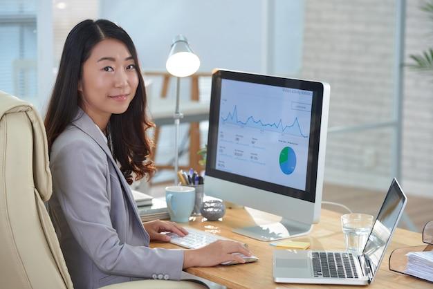 Lächelnde asiatin, die am schreibtisch im büro sitzt und an finanzbericht arbeitet Kostenlose Fotos