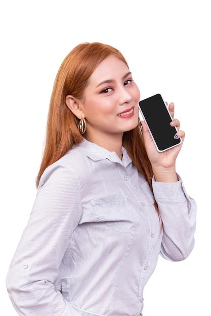 Lächelnde asiatin, die mobilen smartphone mit dem leeren schwarzen schirm steht auf weiß hält Premium Fotos