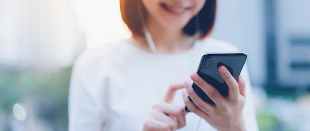 Lächelnde asiatin, die smartphone mit dem hören musik verwendet und im bürogebäude steht Premium Fotos
