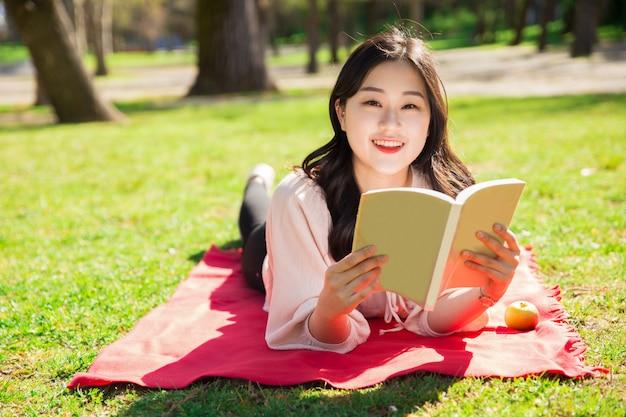 Lächelnde asiatin liegend und lesebuch auf rasen Kostenlose Fotos