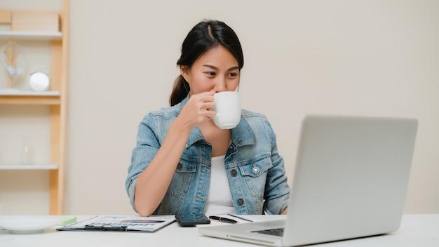 Lächelnde asiatische frau der schönen junge, die zu hause an laptop und trinkendem kaffee im wohnzimmer arbeitet. Kostenlose Fotos