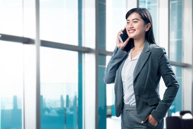 Lächelnde asiatische geschäftsfrau, die an ihrem handy spricht Premium Fotos