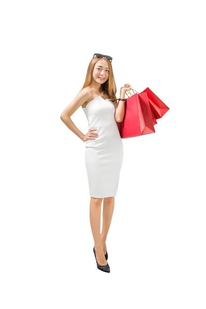 Lächelnde asiatische luxusfrau, welche die rote einkaufstaschestellung trägt Premium Fotos