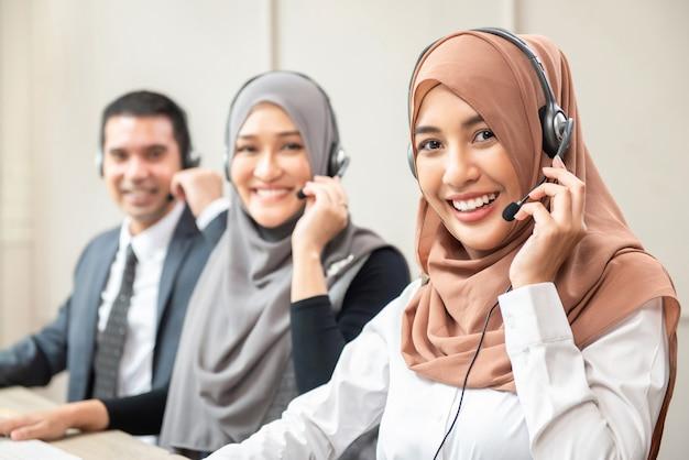 Lächelnde asiatische moslemische frauen, die im kundenkontaktcenter mit team arbeiten Premium Fotos