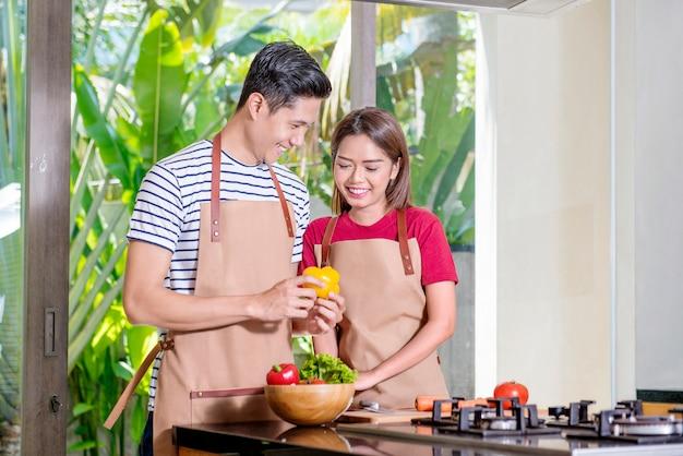 Lächelnde asiatische paare, die für das mittagessen kochen Premium Fotos