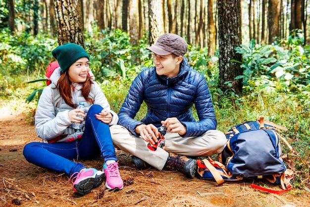 Lächelnde asiatische paarwanderer machen eine pause, während sie ein wasser trinken Premium Fotos