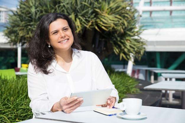 Lächelnde attraktive frau, die tablette im straßencafé bearbeitet und verwendet Kostenlose Fotos