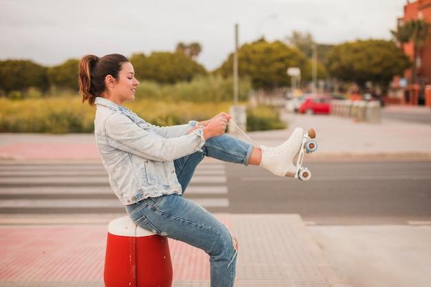 Lächelnde attraktive junge frau, die auf der straße bindet die rollschuhspitze sitzt Kostenlose Fotos