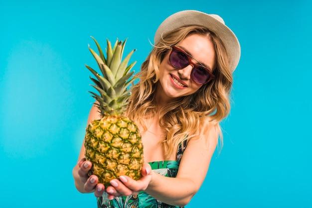 Lächelnde attraktive junge frau im hut und in sonnenbrille, die frische ananas halten Kostenlose Fotos