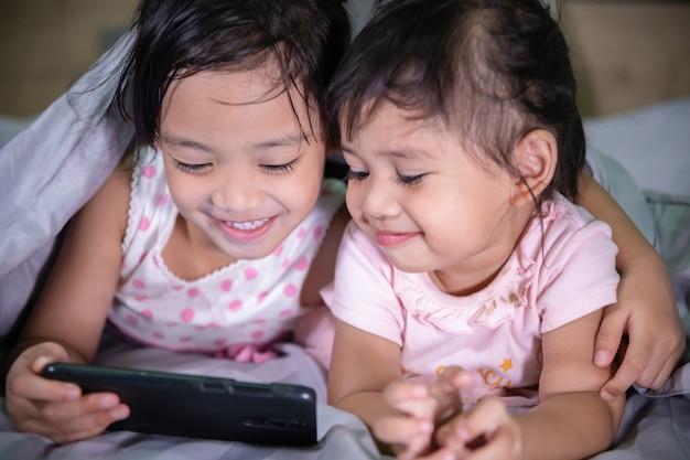 Lächelnde babyschwestern genießen mit einem intelligenten telefon auf dem schlafzimmer Premium Fotos