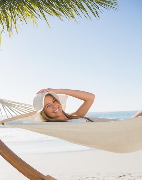 Lächelnde blonde entspannung auf hängematte Premium Fotos